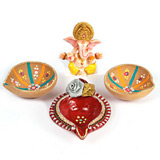 Three large decorated diyas with Ganesh idol