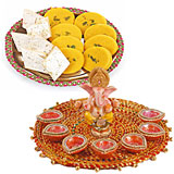Ganpati idol on a tray with 7 diyas and half kilo sweets
