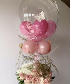 2 pink balloons inside a hot air balloon with 3 pink balloons on the stick tied to 12 Pink and white roses basket
