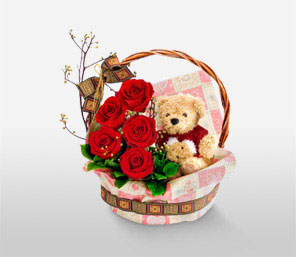 Teddy bear 6 inches with 5 short stems of red roses in the same Basket